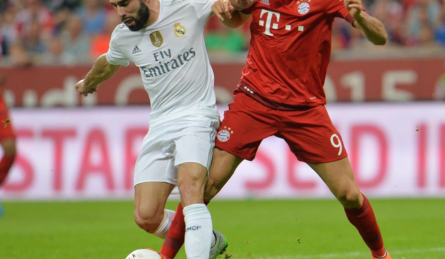 Munichs Robert Lewandowski, right, challenges for the ball with Madrid's Daniel Carvajal during the friendly soccer match between FC Bayern and Real Madrid in the Allianz Arena stadium in Munich, southern Germany, Wednesday, Aug. 5, 2015. (AP Photo/Kerstin Joensson)
