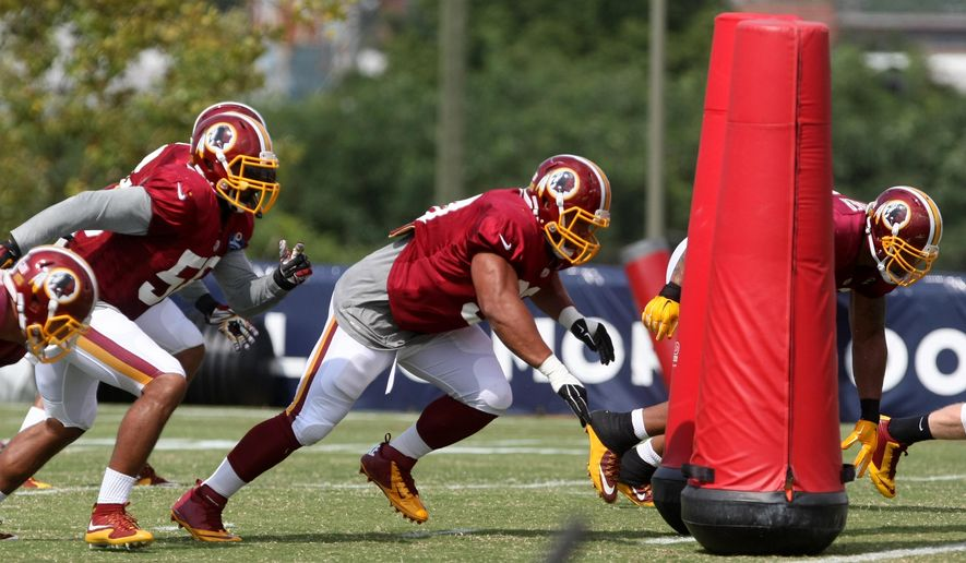 Washington Redskins defensive tackle Stephen Paea, center, and the rest of the defensive line go through drills during the team's NFL football training camp in Richmond, Va., Monday, Aug. 3, 2015.   (AP Photo/Jason Hirschfeld)