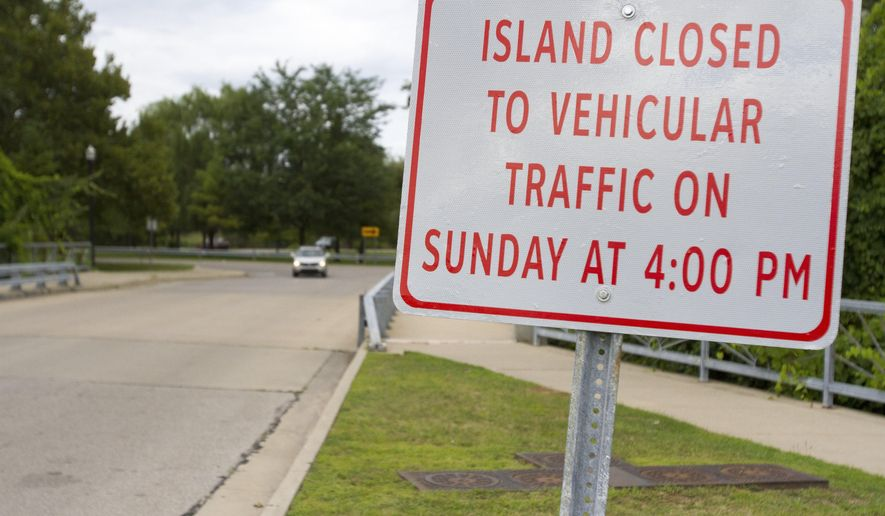 In this photo taken Monday, Aug. 3, 2015, a new sign is seen at the entrance to Ojibway Island in Saginaw, Mich. The new restrictions follow complaints about large groups of people on the island causing problems involving alcohol, loud music and cars. Saginaw police Detective Sgt. Reggie Williams said the new rule is an effort to help manage large crowds on the island. (David C. Bristow/The Saginaw News via AP) ALL LOCAL TELEVISION OUT; LOCAL TELEVISION INTERNET OUT; MANDATORY CREDIT