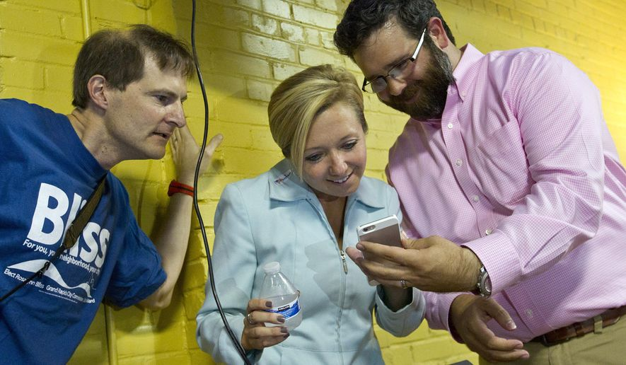 Grand Rapids mayoral candidate Rosalynn Bliss, center, waits for election results with Klaas Kwant, left, and Micahel Lomonaco in Grand Rapids, Mich., Tuesday, Aug. 4, 2015. Bliss was elected the city's 59th mayor according to the The Grand Rapids Press. (Cory Morse/The Grand Rapids Press via AP) ALL LOCAL TELEVISION OUT; LOCAL TELEVISION INTERNET OUT; MANDATORY CREDIT