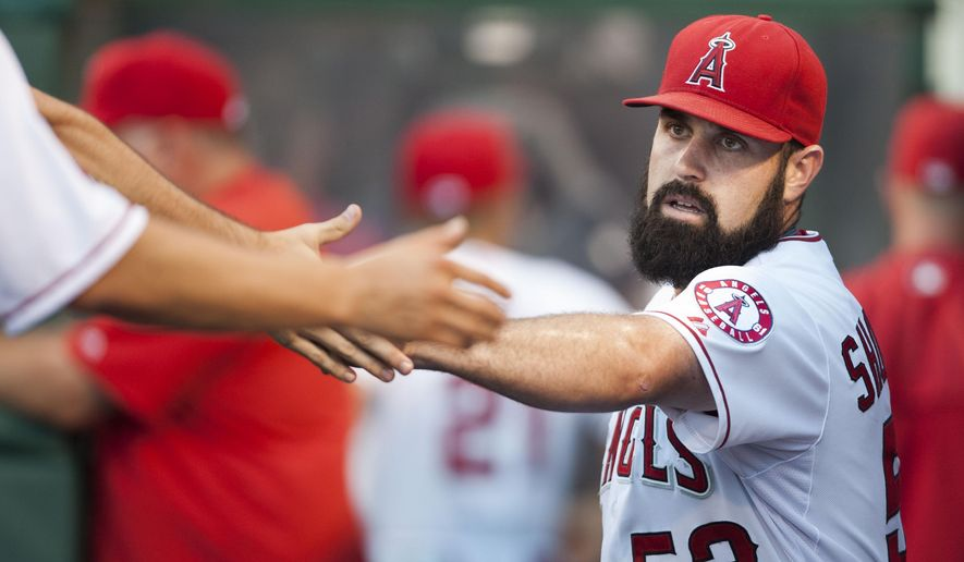 Los Angeles Angels' Matt Shoemaker is greeted in the dugout during the first inning a baseball game against the Cleveland Indians in Anaheim, Calif., Tuesday, Aug. 4, 2015. (Kevin Sullivan/The Orange County Register via AP)   MAGS OUT; LOS ANGELES TIMES OUT; MANDATORY CREDIT