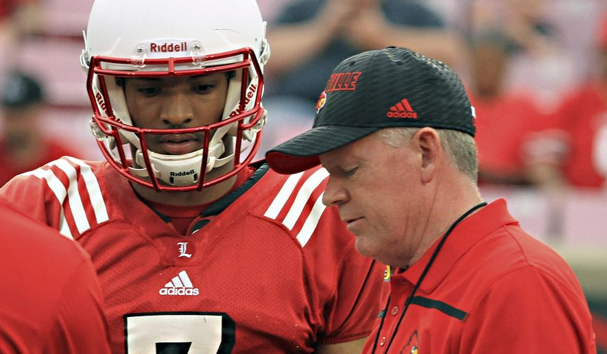 FILE - In this April 17, 2015, file photo, Louisville head football coach Bobby Petrino, right, talks over a play call with quarterback Reggie Bonnafon (7) during the annual spring football scrimmage game at Cardinal Stadium in Louisville, Ky. Having two solid quarterbacks is a good problem to have at first glance, but the task for Louisville coach Bobby Petrino as camp opens in Year 2 is deciding between Reggie Bonnafon and Kyle Bolin and establishing offensive consistency.. (AP Photo/Garry Jones, File)