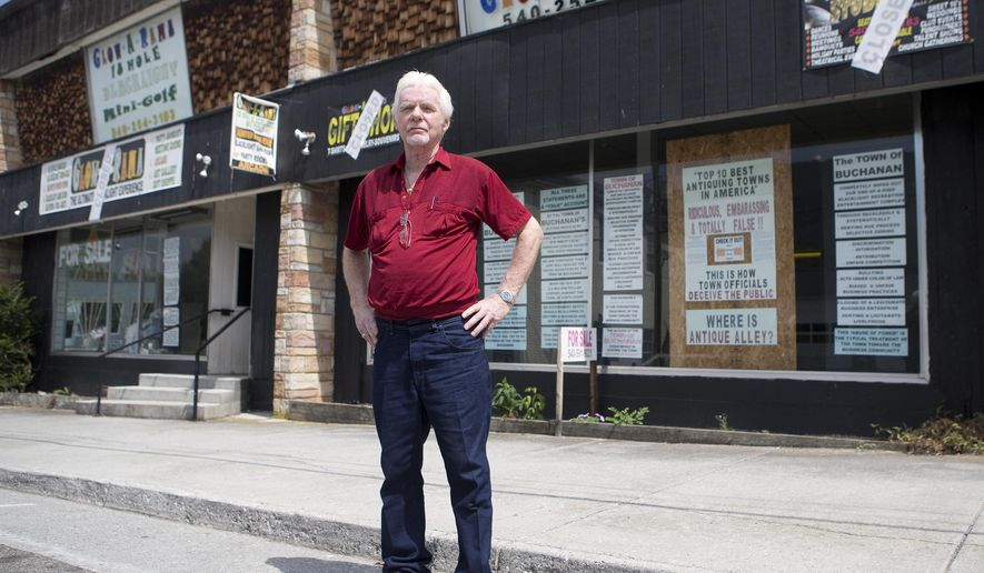 In a Wednesday, July 29, 2015 photo, Ken Bray, 73, stands outside of his business, Glow-A-Rama, in Buchanan, Va. Buchanan officials and Ken and Francine Bray  are at odds over more than a dozen storefront signs that criticize the town. The Buchanan Planning Commission unanimously voted on July 17 to find Ken and Francine Bray in violation of the town's sign ordinance.  Ken Bray said the commission's action is a violation of his First Amendment rights because the signs are a political statement.  (Erica Yoon/The Roanoke Times via AP)