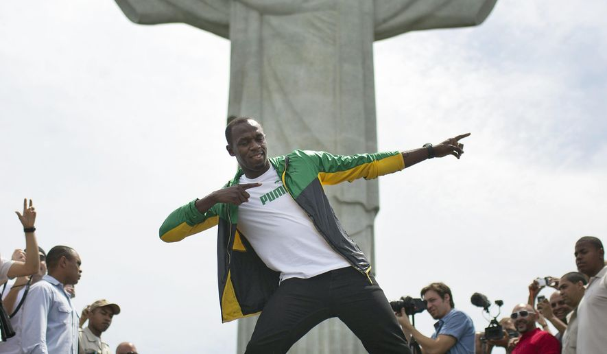 FILE - In this Oct. 23, 2012, file photo, Jamaica's Olympic gold medalist Usain Bolt poses for a photo for the benefit of the media during his visit to the Brazilian landmark Christ the Redeemer statue in Rio de Janeiro, Brazil. A year before the Rio Games, NBC is already seeing indications of more big audiences for the Summer Olympics. (AP Photo/Felipe Dana, File)
