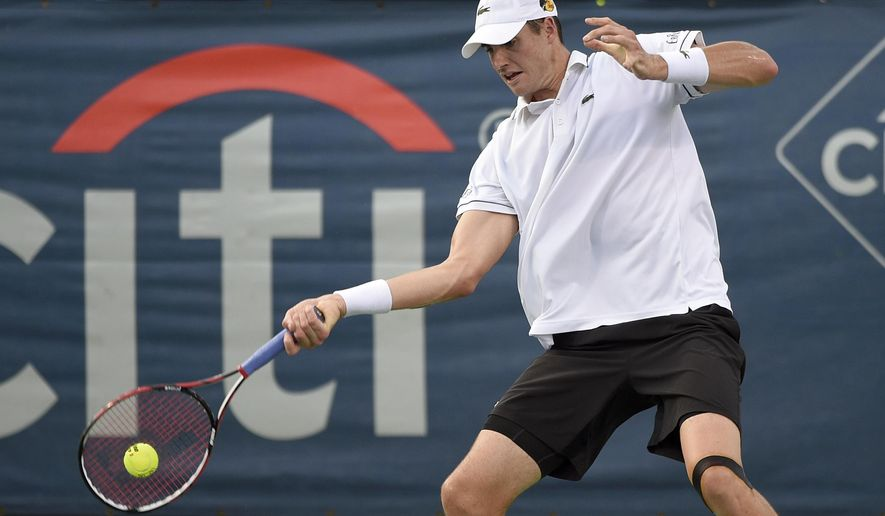 John Isner, of the United States, returns the ball to Victor Estrella Burgos, of the Dominican Republic, at the Citi Open tennis tournament, Wednesday, Aug. 5, 2015, in Washington. (AP Photo/Nick Wass)
