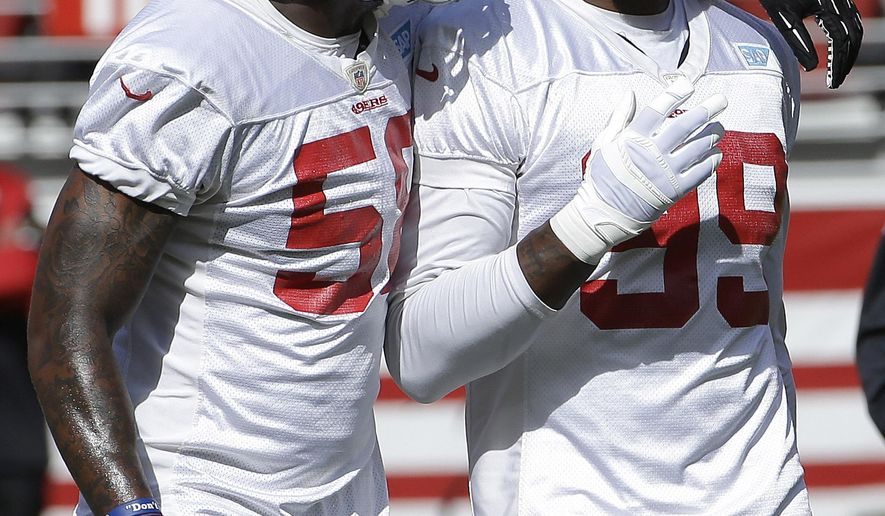 San Francisco 49ers linebackers Eli Harold, left, and Aldon Smith talk during the team's NFL football training camp in Santa Clara, Calif., Sunday, Aug. 2, 2015. (AP Photo/Jeff Chiu)