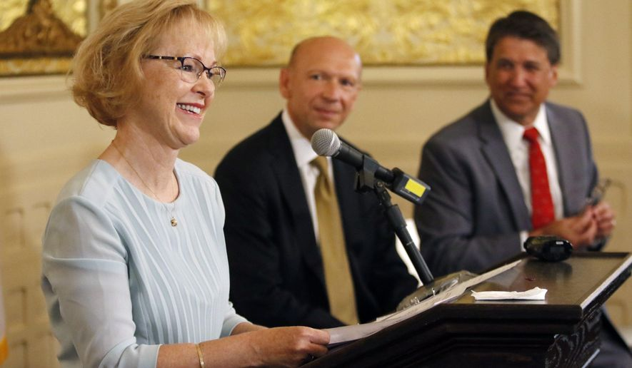 Dr. Aldona Wos, North Carolina's health and human services secretary, thanks her DHHS staffers in the audience for their hard work as Rick Brajer and Gov. Pat McCrory listen during a press conference where she said she was stepping down, Wednesday, Aug. 5, 2015,  at the Governor's Mansion in Raleigh, NC. McCrory introduced Brajer as his choice to replace Wos at the emotional ceremony. Wos will remain on the job for two more weeks.  (Harry Lynch/The News & Observer via AP) MANDATORY CREDIT