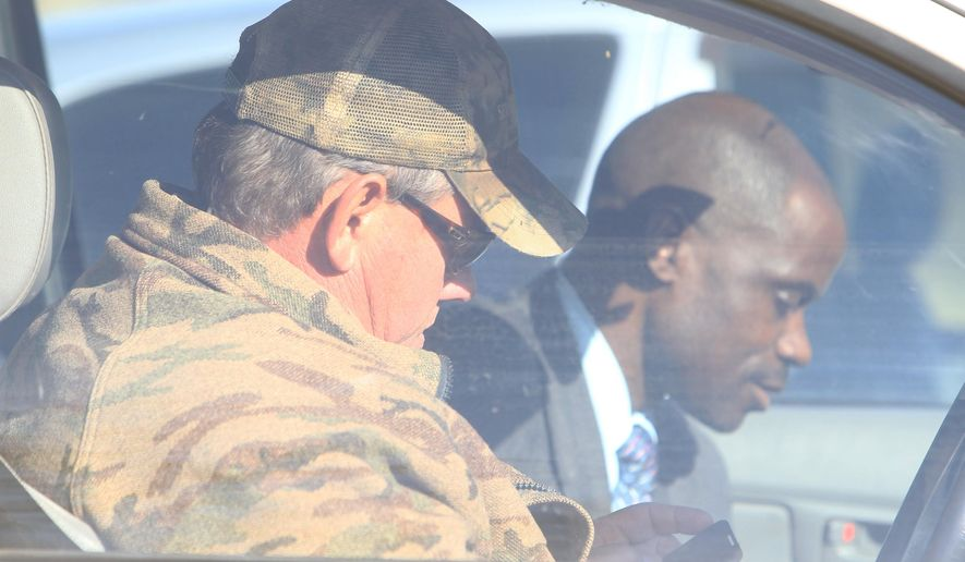 Professional hunter Theodore Bronkhorst is seen in his car with his lawyer Givemore Muvhiringi, back, upon their arrival at the magistrates courts to face trial in Hwange about 700 kilometres south west of Harare, Zimbabwe, Wednesday, Aug. 5, 2015. The trial of a professional hunter who helped an American kill a popular lion named Cecil in an allegedly illegal hunt in Zimbabwe has been postponed to Sept. 28. Theo Bronkhorst appeared Wednesday in a court in Hwange town, where he faces charges of failing to prevent an unlawful hunt. If convicted, he faces up to 15 years in prison. (AP Photo/Tsvangirayi Mukwazhi)