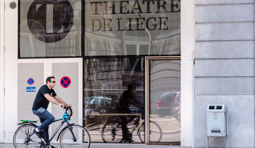 FILE - In this July 31, 2015 file photo, a man rides his bike as he passes the Theatre de Liege, in Liege, Belgium. Japanese designer Kenjiro Sano has refuted claims he copied the emblem of the Belgian theater when he designed the official logo for the 2020 Tokyo Olympics, at a press conference Wednesday, Aug. 5, 2015. (AP Photo/Geert Vanden Wijngaert, File)