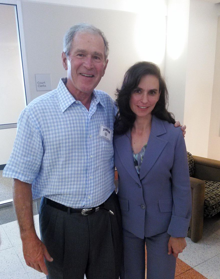 In this photo provided by Terrell Eustice, Eustice, right, poses for a photo with former President George W. Bush who showed up for jury duty in Dallas, Wednesday, Aug. 5, 2015. The 43rd president was not chosen for a jury but did have his picture taken with people before leaving after a few hours. (Courtesy of Terrell Eustice via AP)