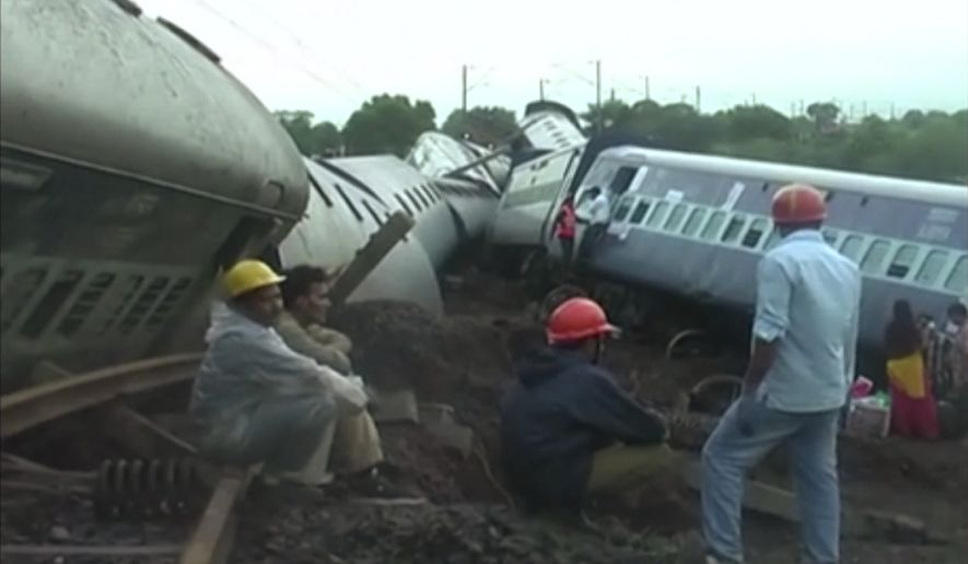 In this image made from video, people gather by two derailed trains in Harda in Madhya Pradesh state, India, Wednesday, Aug. 5, 2015. Two passenger trains derailed over a bridge in central India while crossing a track that was flooded by heavy monsoon rains, killing at a number of people, officials said Wednesday. (Photo via AP Video)