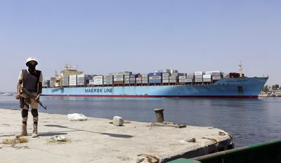 An Egyptian soldier stands guard near the Suez Canal as an American container ship crosses the Suez Canal in Ismailia, Egypt, in this Tuesday, Aug. 12, 2014, file photo. Egypt on Thursday, Aug. 6, 2015, will unveil a major extension of the Suez Canal, a mega-project that has emerged as a cornerstone of President Abdel-Fattah el-Sissi's efforts to restore national pride and revive the economy after years of unrest. (AP Photo/Amr Nabil, File)