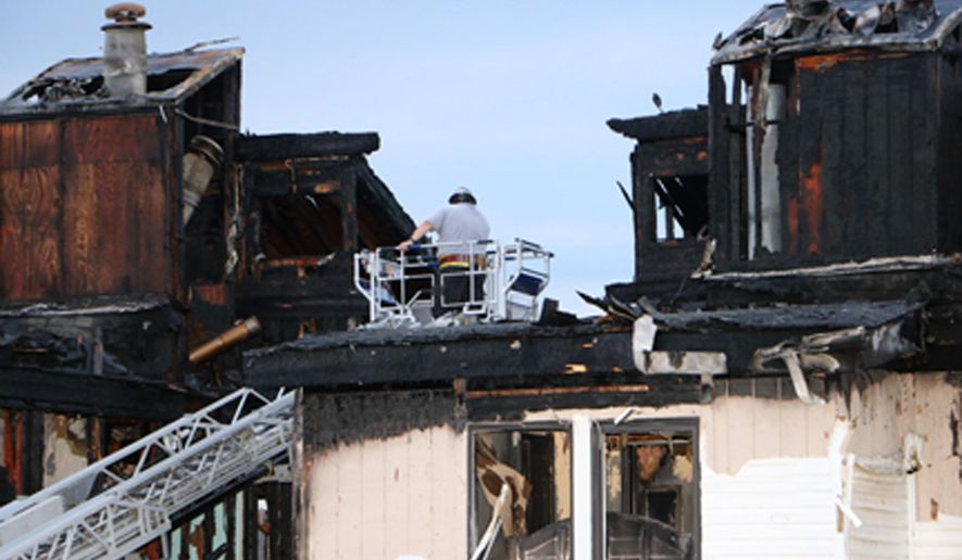 In this photo provided by Dan Field, a fire investigator surveys the aftermath of an overnight fire Wednesday, Aug. 5, 2015 in Osage Beach, Mo. Authorities said the fire swept through the top floor of the four-story condominium killing four young children. (Dan Field/Lake Media via AP) MANDATORY CREDIT