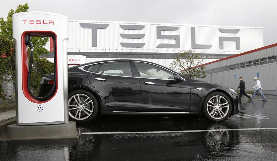 In this May 14, 2015 photo, a Tesla vehicle is parked at a charging station outside of the Tesla factory in Fremont, Calif. Tesla reports quarterly financial results on Wednesday, Aug. 5, 2015. (AP Photo/Jeff Chiu)