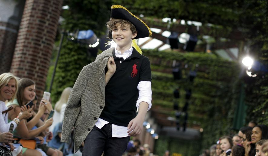 "Levi Miller, star of the upcoming film ""Pan,"" walks the runway wearing Ralph Lauren children's Fall fashion, Wednesday, Aug. 5, 2015, in New York. Polo hosted the show to promote children's literacy but also to promote the October film, ""Pan,"" which is Peter Pan's origin story. (AP Photo/Julie Jacobson)"