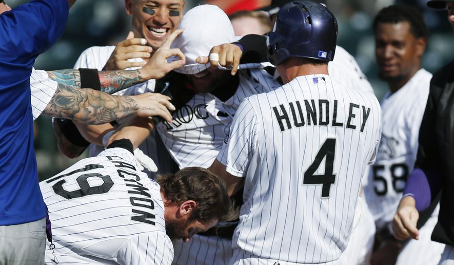 Colorado Rockies' Michael McKenry, center, has his jersey pulled over his head by a teammate as Charlie Blackmon, front left, and Nick Hundley join in the celebration after McKenry's two-run home run against the Seattle Mariners during the 11th inning of a baseball game Wednesday, Aug. 5, 2015, in Denver. Colorado won 7-5 in 11 innings. (AP Photo/David Zalubowski)