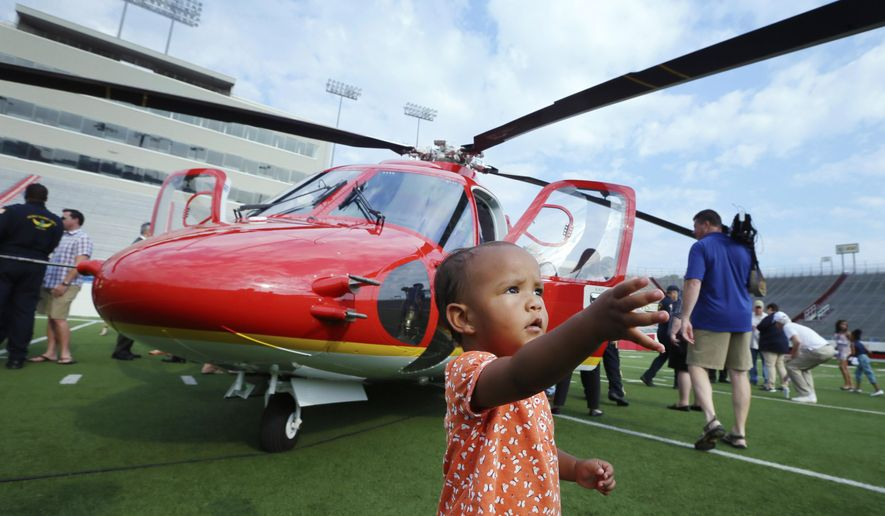 Carrie Ospring, 1, walks past one of Arkansas Children's Hospital's two new Sikorsky S-76 D helicopters at War Memorial Stadium in Little Rock, Ark., Wednesday, Aug. 5, 2015. The two aircraft are to replace earlier models in service since 2002. (AP Photo/Danny Johnston)