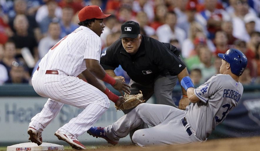 Philadelphia Phillies third baseman Maikel Franco, left, tags out Los Angeles Dodgers' Joc Pederson, right, after Pederson tried to advance to third base on a single by Alberto Callaspo during the fourth inning of a baseball game, Wednesday, Aug. 5, 2015, in Philadelphia. At center is umpire Brian O'Nora. (AP Photo/Matt Slocum)
