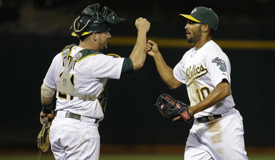 Oakland Athletics shortstop Marcus Semien, right, is greeted by catcher Stephen Vogt at the end of the A's baseball game against the Baltimore Orioles on Tuesday, Aug. 4, 2015, in Oakland, Calif. Oakland won 5-0. (AP Photo/Eric Risberg)