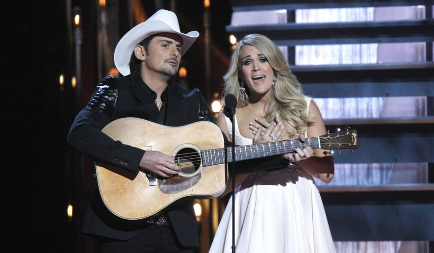 In this Nov. 5, 2014, file photo, Brad Paisley, left, and Carrie Underwood perform as they host the 48th annual CMA Awards in Nashville, Tenn. Underwood and Paisley will return to host the Country Music Association Awards on ABC this fall for an eighth straight year. The 49th annual awards show will air live from Bridgestone Arena in Nashville, Tenn., on Nov. 4. (Photo by Wade Payne/Invision/AP, File)