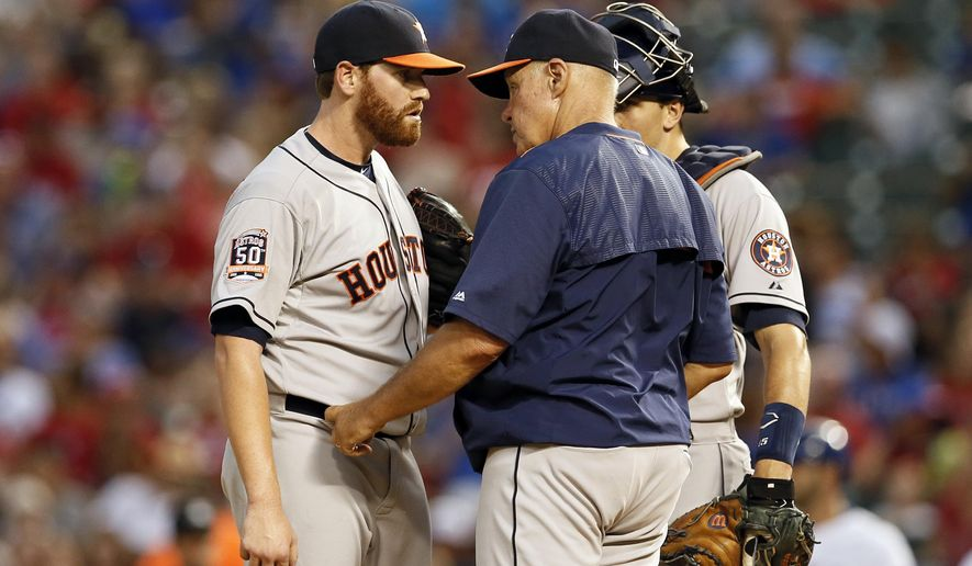 Houston Astros starting pitcher Dan Straily talks with pitching coach Brent Strom, center, as catcher Jason Castro listens in the fourth inning of a baseball game against the Texas Rangers Tuesday, Aug. 4, 2015, in Arlington, Texas. (AP Photo/Tony Gutierrez)