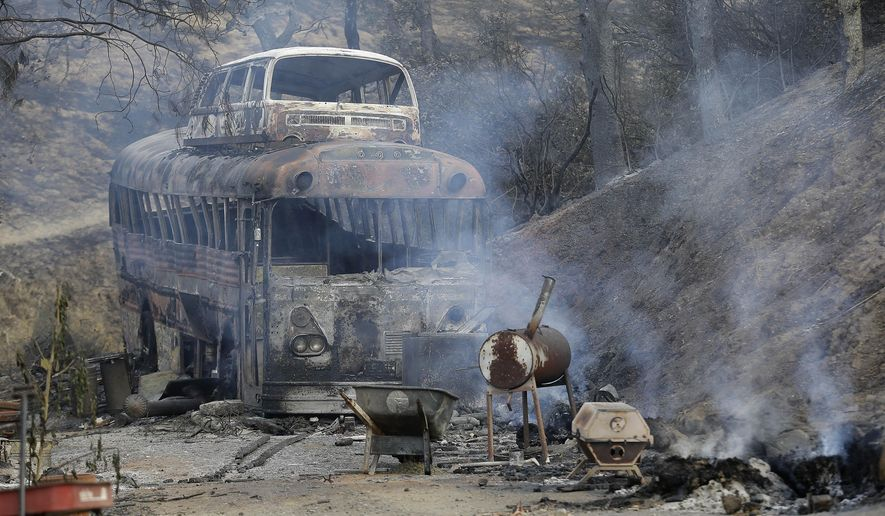 A burned bus is shown near Clearlake, Calif., Wednesday, Aug. 5, 2015. Thousands of firefighters battling an unruly Northern California wildfire were aided overnight by cooler temperatures and higher humidity, but the fire is still less than a quarter contained. (AP Photo/Jeff Chiu)