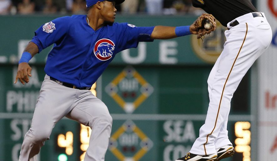Pittsburgh Pirates' Neil Walker, right, leaps to avoid the tag by Chicago Cubs' Addison Russell during a run down between second and third in the fourth inning of a baseball game, Wednesday, Aug. 5, 2015, in Pittsburgh. Walker was ruled out for being out of the baseline. (AP Photo/Gene J. Puskar)