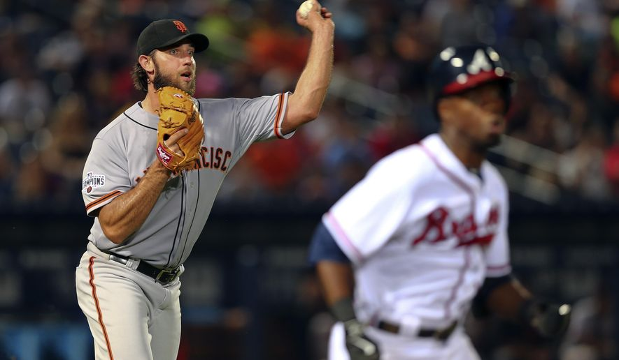 San Francisco Giants starting pitcher Madison Bumgarner (40) throws to first but not in time to retire Atlanta Braves' Eury Perez, foreground, in the eighth inning of a baseball game, Wednesday, Aug. 5, 2015, in Atlanta. (AP Photo/John Bazemore)