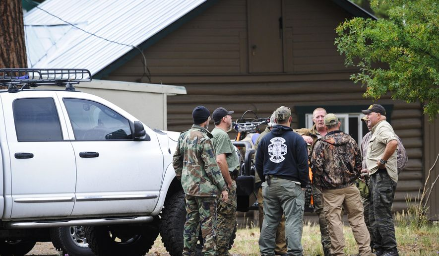Self-described constitutional rights activists confer Wednesday Aug. 5, 2015, just off Main St. in Lincoln, Mont. Members of armed groups that call themselves constitutional advocates have arrived in Lincoln to support an owner during an ongoing dispute with the U.S. Forest Service concerning a federal mining claim. (Thom Bridge/The Independent Record via AP) MANDATORY CREDIT
