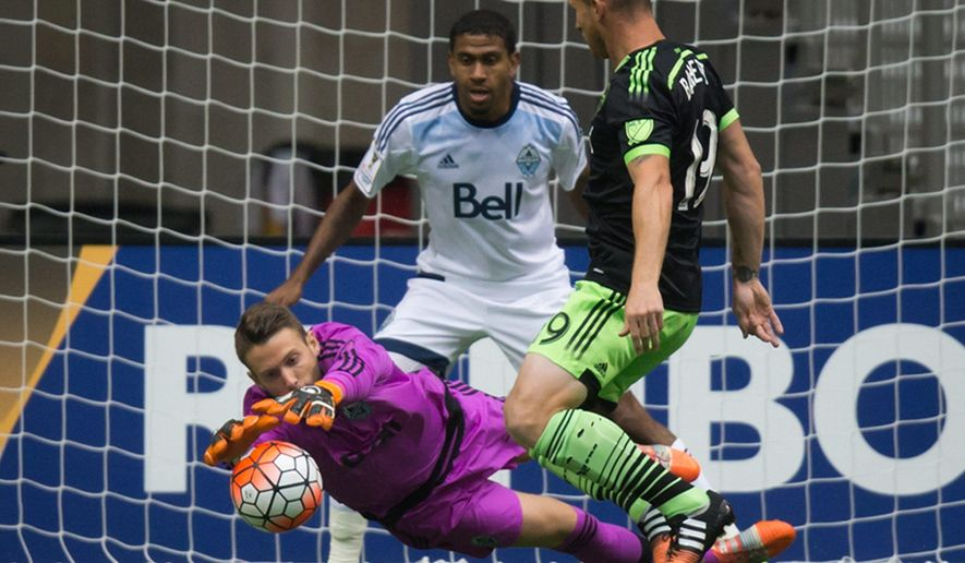 Vancouver Whitecaps goalkeeper Paolo Tornaghi, bottom left, of Italy, dives to keep the ball away from Seattle Sounders' Chad Barrett, right, as Whitecaps' Ethen Sampson, back, defends during the first half of a CONCACAF Champions League soccer game Wednesday, Aug. 5, 2015, in Vancouver, British Columbia. (Darryl Dyck/The Canadian Press via AP)