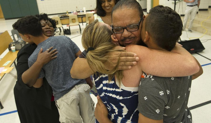 ADVANCED FOR RELEASE SATURDAY, AUGUST 8, 2015 Keith Beatty, center, embraces Elizabeth Scott, left, and her son Leland, after the trio participated in a prayer circle during a Sunday, June 7, 2015, service at Kingdom Promises Church in Gilbert, Ariz. Beatty, a former resident of York, Pa., moved to Arizona to build the church with his wife Sylvia, center rear, who is the pastor, and other onetime residents of York, Pa., including Scott and her son followed the couple there. (Jason Plotkin/Daily Record/Sunday News via AP)