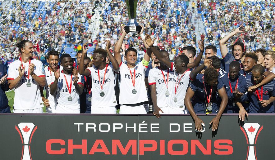 Paris Saint-Germain captain Thiago Silva, centre, along with teammates raise the Champions Trophy after defeating Olympique Lyonnais in Montreal, Saturday, Aug. 1, 2015. (Graham Hughes/The Canadian Press via AP)
