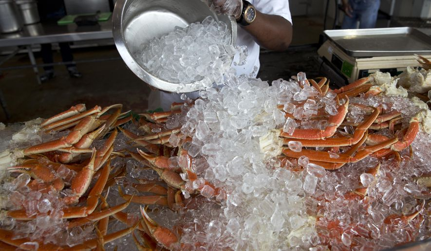 Antoine Saint-eyr covers jumbo crab legs with ice at Captain White's fresh seafood market at The Wharf along the Washington Cannel in Washington, Thursday, July 30, 2015. (AP Photo/Carolyn Kaster)  **FILE**