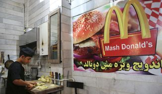 """In this Wednesday, Aug. 5, 2015 photo, Iranian worker Shahin Mirouzadeh cuts potatoes at """"Mash Donald's"""" fast food restaurant, a knock-off version of McDonald's in western Tehran, Iran. (AP Photo/Vahid Salemi)"""