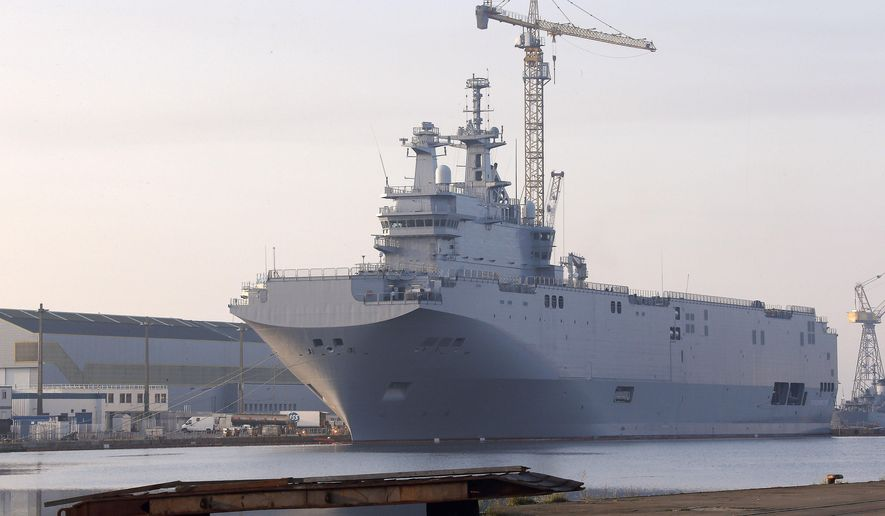 """FILE -  In this Friday, Sept. 5, 2014 file photo, the Vladivostok warship, the first of two Mistral-class helicopter carriers ordered by Russia, docks on the port of Saint-Nazaire, western France. After France reached agreement to cancel the sale of two warships it had been building for Russia, the French Defense minister was on the radio Thursday, Aug. 6, 2015 talking up their merits. Jean-Yves Le Drian said a number of unspecified countries already have """"made their interest known"""" in the Mistrals, which are similar to the U.S. Navy's San Antonio class of amphibious transport dock ships.(AP Photo/David Vincent, File)"""