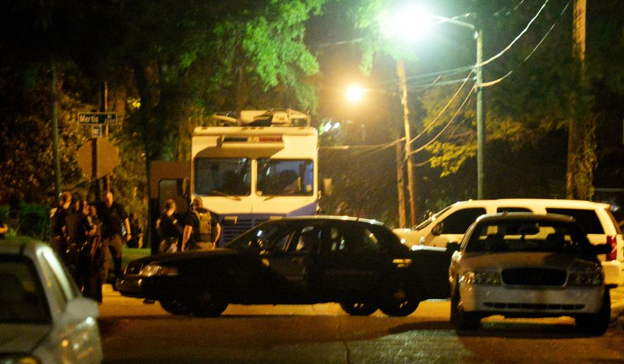 Law enforcement officials surround the scene where a Shreveport police officer was shot Wednesday, Aug. 5, 2015, in Shreveport, La. Police in northwest Louisiana say an officer has died after being shot while on duty, and a manhunt for a suspect is under way. (Henrietta Wildsmith/The Shreveport Times via AP)