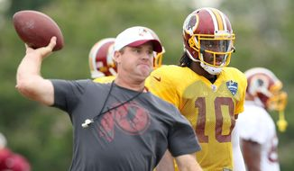Washington Redskins quarterback Robert Griffin III watches as coach Jay Gruden throws to receivers at an NFL training camp Thursday, Aug. 6, 2015, in Richmond, Va. The Washington Redskins and Houston Texans begin three days of joint workouts at the Redskins' training complex. (Rob Ostermaier/The Daily Press via AP) MANDATORY CREDIT