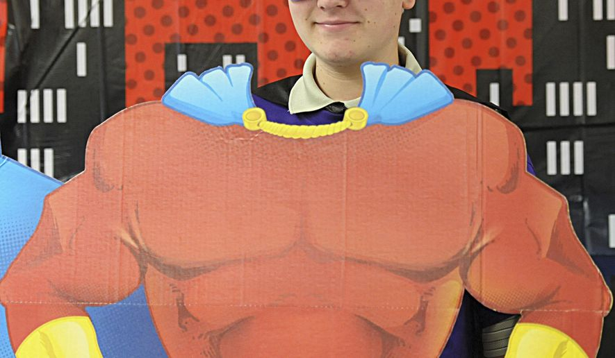 In this June 17. 2015  photo, Jonathin Brandner, 17, of Granville poses behind a cardboard cutout of Superman at the Teen Summit, a superhero-themed event at the La Salle County Housing Authority's Centennial Courts Community Center in La Salle, Ill. During this day, each participant received a T-shirt, hat, bag, a copy of a superhero video and many other items. (Scott Anderson/NewsTribune via AP)