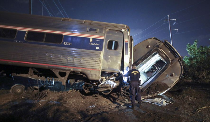 In this May 12, 2015, file photo, emergency personnel work the scene of a deadly train wreck in Philadelphia. Only a handful of railroads are close to meeting a deadline this year to install safety technology that can prevent many crashes, including derailments due to excessive speed like the deadly Amtrak crash in Philadelphia in May, according to a government report released Friday. (AP Photo/ Joseph Kaczmarek, File)