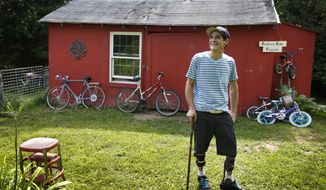 In Thursday, July 30, 2015 photo Ryan Kinsella poses outside his bicycle repair business in Penobscot, Maine. Kinsella broke his back in a rock climbing accident in 2002. The accident left him with partially paralyzed legs. He is recovering from a long battle with hepatitis C., which he contracted by sharing IV drug needles. The rise of cheap heroin has brought a rise in hepatitis C. Perhaps nowhere is the problem starker than in Downeast Maine, which has the highest hepatitis C rate in a state with quintuple the national average. (AP Photo/Robert F. Bukaty)