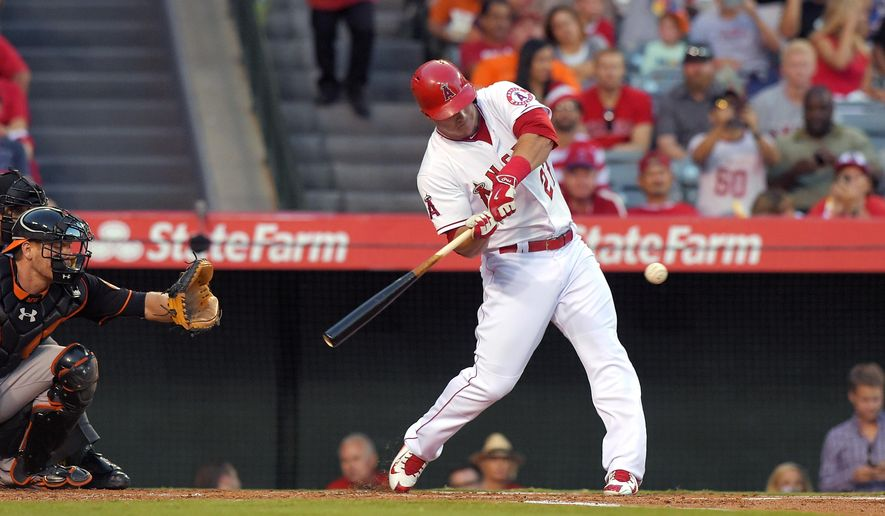 Los Angeles Angels' Mike Trout, right, hits a solo home run as Baltimore Orioles catcher Matt Wieters watches during the first inning of a baseball game, Friday, Aug. 7, 2015, in Anaheim, Calif. (AP Photo/Mark J. Terrill)