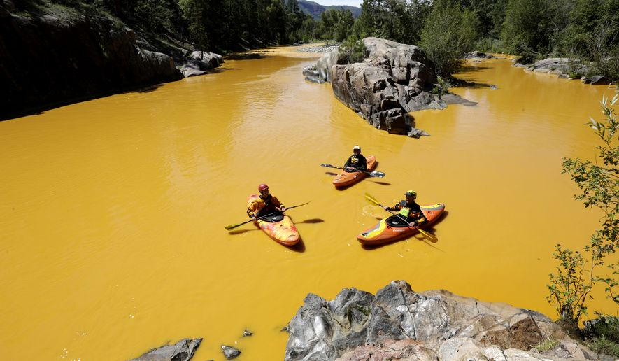 People kayak in the Animas River near Durango, Colo., on Aug. 6, 2015, in water colored from a mine waste spill. The U.S. Environmental Protection Agency said that a cleanup team was working with heavy equipment Wednesday to secure an entrance to the Gold King Mine. Workers instead released an estimated 1 million gallons of mine waste into Cement Creek, which flows into the Animas River. (Jerry McBride/The Durango Herald via Associated Press)