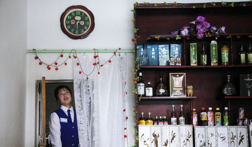 A North Korean waitress walks through a door under a clock with Chinese emblems at a restaurant in Rason city in North Korea, in this Aug. 29, 2011, photo. North Korea said Friday, Aug. 7, 2015, that it will establish its own time zone next week by pulling back its current standard time by 30 minutes. (AP Photo/Ng Han Guan, File)