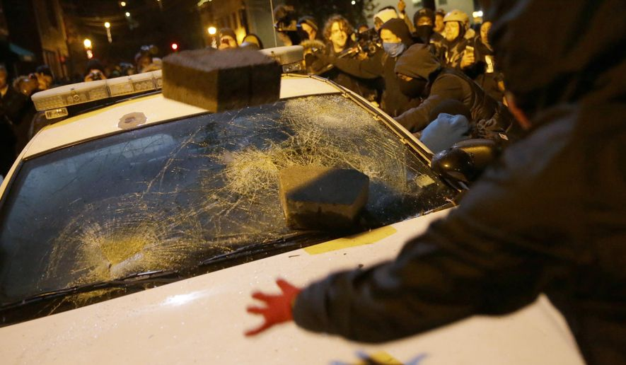 In this Nov. 25, 2014, file photo, protesters vandalize a police vehicle outside of Ferguson city hall in Ferguson, Mo. (AP Photo/David Goldman, File)