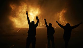 "In this Nov. 25, 2014, file photo, people watch as stores burn in Ferguson, Mo. The one-year anniversary of the shooting of Michael Brown, which sparked months of nationwide protests and launched the ""Black Lives Matter"" movement, was on Sunday, Aug. 9, 2015. (AP Photo/David Goldman, File)"