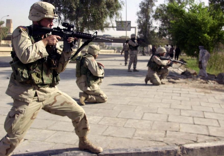 In this Oct. 4, 2003, file photo, American soldiers aim toward a stone-throwing mob of ex-Iraqi soldiers near a former military airport in central Baghdad, Iraq. (AP Photo/Khalid Mohammed, File)