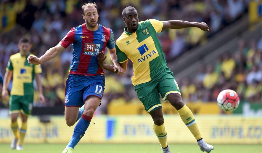 Norwich City's Sebastien Bassong, right, and Crystal Palace's Glenn Murray battle for the ball during their  Premier League match at Carrow Road, Norwich England Saturday Aug. 8, 2015 . (Adam Davy/PA via AP) UNITED KINGDOM OUT