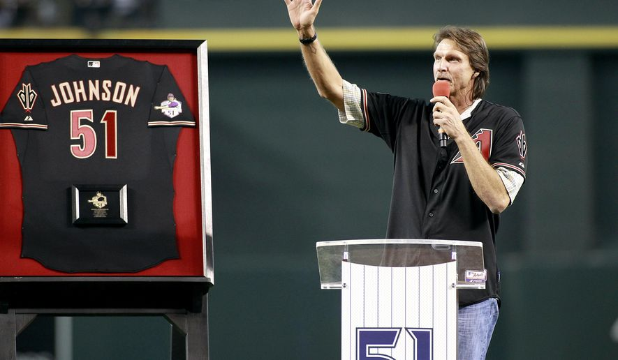 Hall of Fame pitcher Randy Johnson waves to the crowd during a ceremony retiring his No. 51 Arizona Diamondbacks jersey, before a baseball game between the Cincinnati Reds and the Diamondbacks, Saturday, Aug. 8, 2015, in Phoenix. (AP Photo/Ralph Freso)