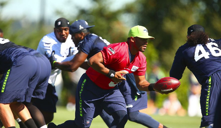 Seattle Seahawks quarterback Russell Wilson runs a play during NFL football training camp Friday, Aug. 7, 2015, in Renton, Wash. (John Lok/The Seattle Times via AP)