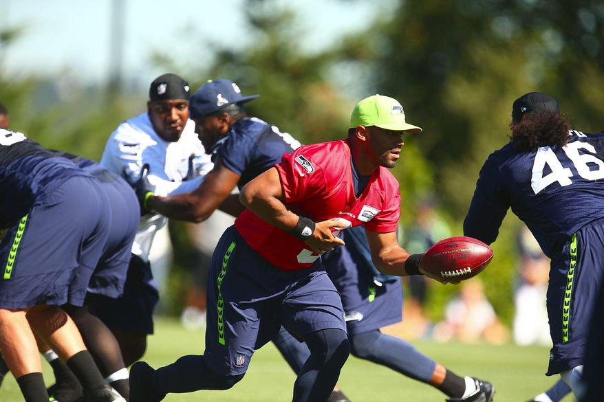 Seattle Seahawks quarterback Russell Wilson runs a play during NFL football training camp Friday, Aug. 7, 2015, in Renton, Wash. (John Lok/The Seattle Times via AP)
